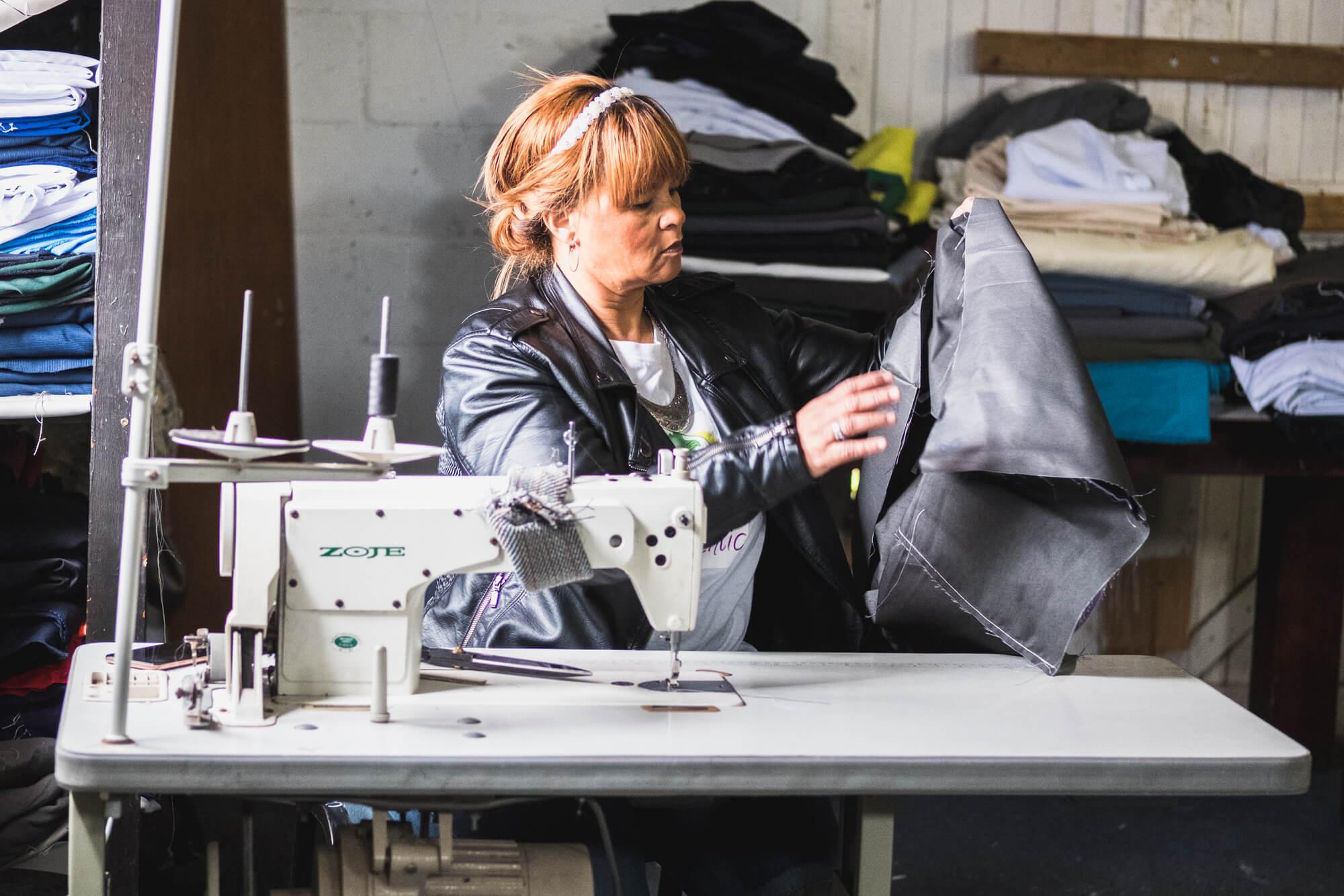 Een van de naaisters in de productiefaciliteit WYAP.