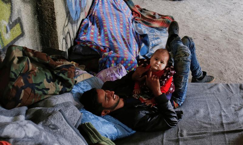 Vluchtelingen zoeken onderdak in een verlaten gebouw in Sarajevo. Foto: Amel Emric/AP, NRC.