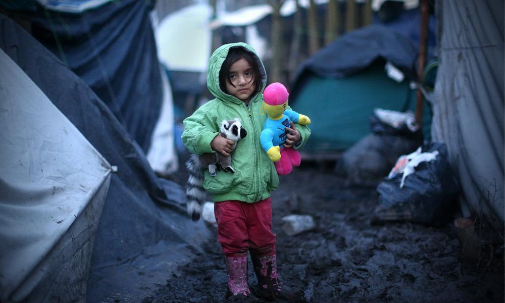 Een jong Koerdisch meisje met haar speelgoed in de modder. Foto: Carl Court/Getty Images.